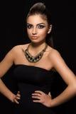 Vogue. Härlig kvinna som poserar i svart klänning Arkivfoto