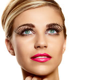 Vogue long lashes. Beautiful young blond woman face closeup wearing vogue long lashes and bright pink lipstick - naturally beautiful skin texture stock images