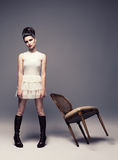 Vogue look. Beautiful young lady posing on gray background with a retro chair Stock Images