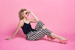 Vogue model posing on floor of studio. Young vogue model i nstriped pants and sunglasses posing on floor sensually Royalty Free Stock Images