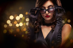 Vogue style close-up portrait of beautiful woman. Long curly brunette hair on black background with lights. St valentine Royalty Free Stock Image