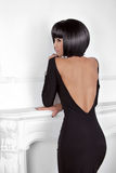 Vogue Style. Fashion Beauty Woman in sexy dress showing back. Br. Unette Lady with Black Short Hair Styling posing behind modern wall Stock Image