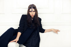 Vogue style portrait of beautiful brunette woman on a sofa with Royalty Free Stock Photography