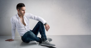 Vogue style of young man. Resting on floor Stock Photo