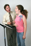 Voice Lesson Diaphragm. A voice teacher showing a student how to breath from her diaphragm Royalty Free Stock Image