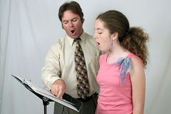 Voice Lesson Ohhhh Sound. A voice teacher demonstrating to a student how to make the Ohhh sound Royalty Free Stock Photos