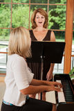Voice Lessons. Voice teacher giving lessons to a mature adult student Royalty Free Stock Images