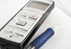 Voice recorder. With pen on a notebook Royalty Free Stock Photo