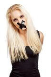 Voiceless Woman in a Struggle for Her Freedom. Voiceless woman with a duct tape over her mouth in a struggle for her freedom of expression royalty free stock photos