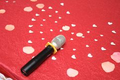 Voices of love as represented by a microphone and heart-shaped paper cuts Royalty Free Stock Photography