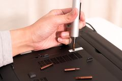 The void of warranty after women repair laptop using screw driver, repair and maintenance Royalty Free Stock Photos