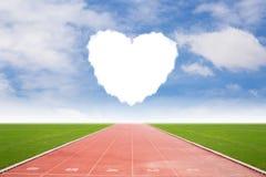 Voie courante dans le stade avec la forme de nuage de coeur Photographie stock libre de droits