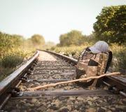 Voie de chemin de fer croisant le paysage rural avec le sac à dos de voyage Photo stock