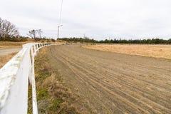 Voie de course vide pour des chevaux d'emballage, voie de sable et barrière blanche Images stock