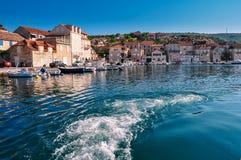 Voie de mousse derrière le bateau dans la baie de mer de petite ville Photo stock