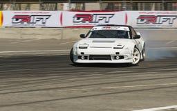 Voie de tour surmontée par Nissan de marque de voiture de dérive Photo stock
