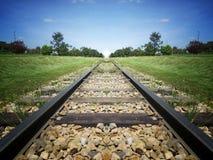 Voie de train au ciel sur le champ en bois d'herbe verte photographie stock libre de droits