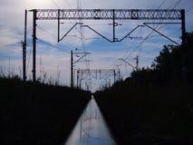 Voie ferroviaire reflétant l'infrastructure de ciel bleu et de chemin de fer Photographie stock