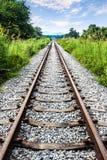 Voies de chemin de fer avec l'herbe verte, la montagne et le ciel bleu, Thaïlande. photos libres de droits