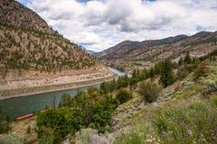 Voies de Railrod fonctionnant des deux côtés d'une rivière dans les montagnes et le ciel nuageux photographie stock libre de droits
