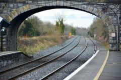 Voies de train allant sous le vieux pont en pierre Photo stock