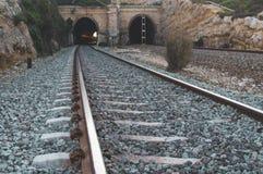 Voies de train et fond de tunnel avec des réflexions de la lumière images stock