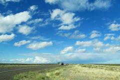 Voies et voitures sur une longue route à l'horizon de ciel Photographie stock libre de droits