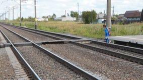 Voies ferroviaires de croisement de femme après arrivée à la station banque de vidéos
