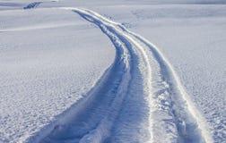Voies sur la glace de rivière d'un motoneige images libres de droits