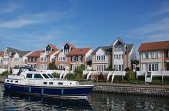 Voiles de bateau à travers des maisons Image stock