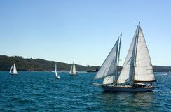Voilier avec les voiles ouvertes croisant au-dessus de l'eau variable en Sydney Harbor, Australie photographie stock