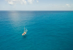 Voilier dans l'eau bleue lumineuse - vue aérienne - Isla Mujeres, Mexique Photographie stock