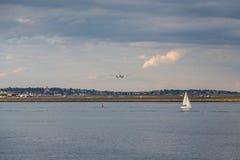 Voilier et avion sous des nuages de tempête Photos stock