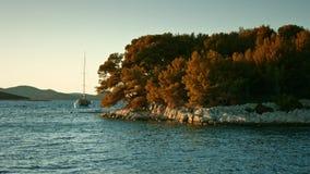 Voilier flottant sur la mer pendant le coucher du soleil Littoral à l'arrière-plan banque de vidéos