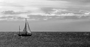 Voilier sur l'Océan Atlantique sous un ciel nuageux noir et blanc Photographie stock