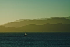 Voilier sur la navigation d'océan dans le coucher du soleil Image libre de droits