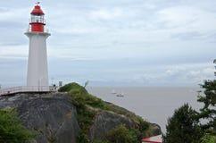 Voiliers dans la mer et le phare sur la roche de littoral photo stock