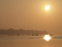 Voiliers sur l'eau au coucher du soleil Image stock