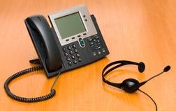 VoIP Telefon mit einem Kopfhörer Lizenzfreie Stockbilder