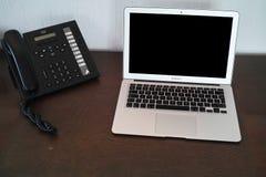 VoIP telefon nära bärbar datordatoren Arkivbilder