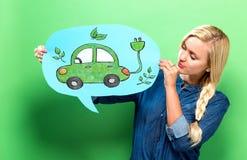 Voiture électrique avec la femme tenant une bulle de la parole Image stock