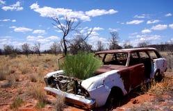 Voiture abandonnée, désert aride, plantes vertes Image libre de droits