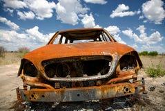 Voiture abandonnée dans le domaine sous le ciel bleu Image stock