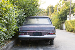 Voiture abandonnée garée près de l'arbre Photo stock