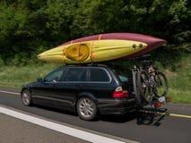 Voiture avec des kayaks sur le dessus et des bicyclettes sur le dos allant pour des vacances photographie stock libre de droits