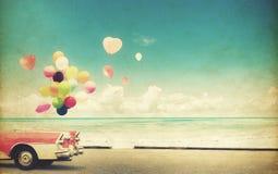 voiture avec le ballon de coeur sur le ciel bleu de plage Photo libre de droits