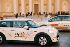 Voiture blanche Mini Cooper With Logo Citybee de couleur passant la rue Photos libres de droits