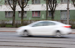 Voiture blanche mobile avec l'effet de tache floue de mouvement Photos stock