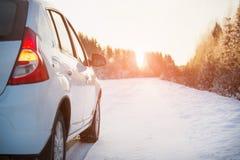 Voiture blanche sur une route d'hiver Photographie stock