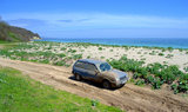 Voiture bleue couverte dans la boue sur le chemin de terre à une plage Photos libres de droits